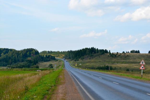 Autobahn durch ein feld und wald gegen den himmel.