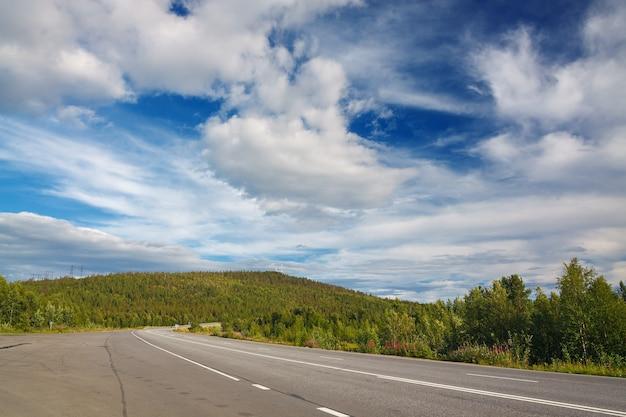 Autobahn mit markierungen auf dem himmelshintergrund