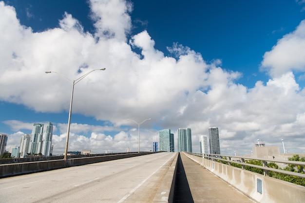 Autobahn oder öffentliche straße für transportfahrzeuge und städtische wolkenkratzer auf bewölktem hintergrund des blauen himmels