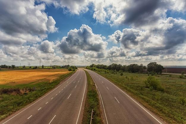 Autobahn von der höhe der brücke, vor dem hintergrund von wolken, feldern und blauem himmel