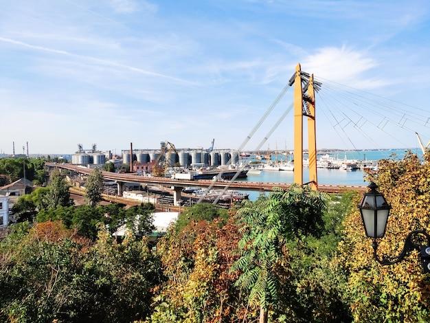 Autobahnbrücke, eisenbahn auf seehafen, hafen mit aufzügen yachten schiffe schwimmende frachtkräne. konzept der logistischen transportbranche.