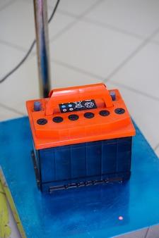 Autobatterie steht auf bodenwaagen vor dem hintergrund eines verschwommenen gestells.