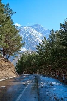 Autobergstraße im frühjahr mit atemberaubendem blick auf den berg mit schneekappe auf der spitze.