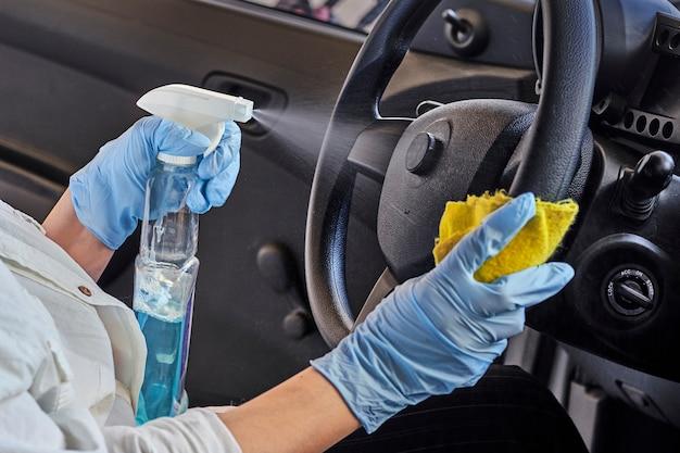 Autodesinfektionsservice. fahrzeuginnenraum reinigen und mit desinfektionsflüssigkeit besprühen