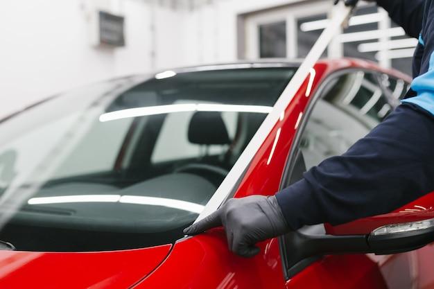 Autodetaillierung - mann, der im laden für das polieren von autos arbeitet. selektiver fokus.