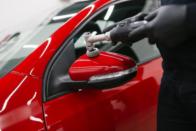 Autodetaillierung - mann mit orbitalpolierer in der werkstatt, die auto poliert. selektiver fokus.