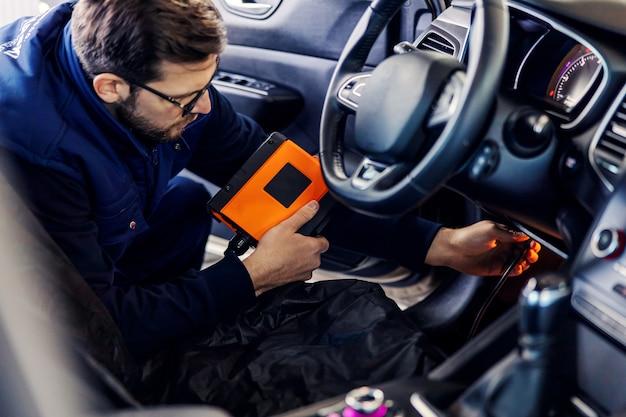 Autodiagnose bei technischer inspektion, autoelektronik. ein mann in blauer uniform hält ein digitalisierungsgerät und prüft den zustand der schnur im auto unter dem lenkrad