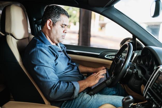 Autodiagnose. technische inspektion, autoelektronik. ein lateinischer mann hält ein digitalisierungsgerät.