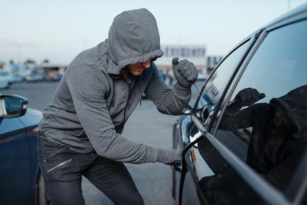 Autodieb, der türschloss bricht, krimineller job, einbrecher. männliches räuberöffnungsfahrzeug mit kapuze auf dem parkplatz.