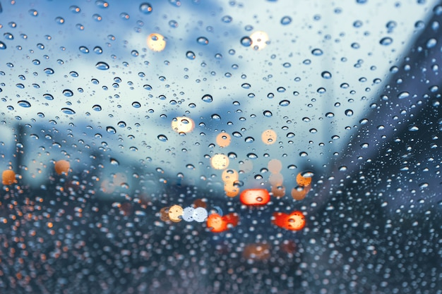 Autofahren auf metropolenstraße im verkehrsstau mit regentropfen über der windschutzscheibe