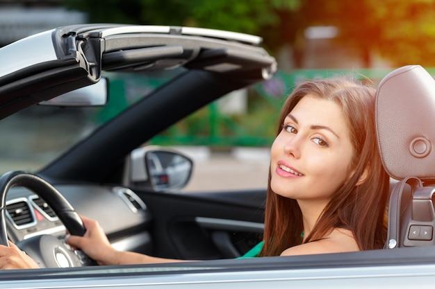Autofahren der jungen frau in der stadt.