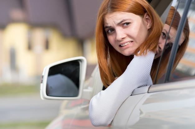Autofahren der jungen frau rückwärts. mädchen mit lustigem ausdruck auf ihrem gesicht, während sie einen kotflügelbiegeschaden an einem hinteren fahrzeug anrichtete.
