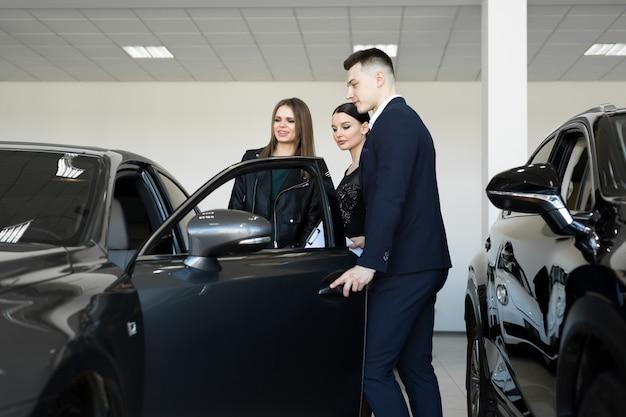 Autogeschäft, autoverkauf - ein paar freunde von mädchen mit einem autohändler wählen ein auto in einem autohaus