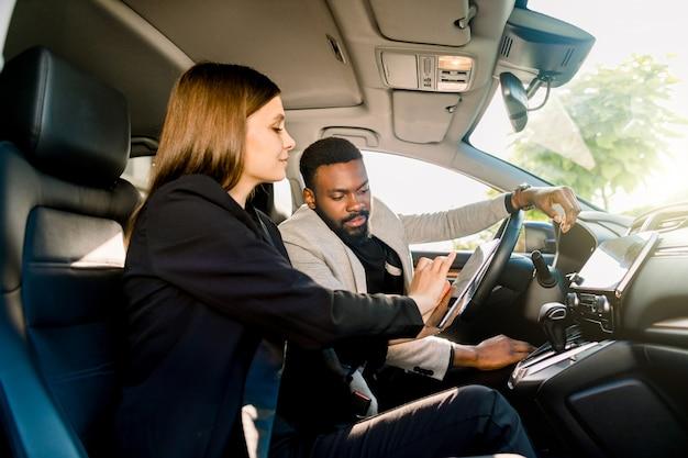 Autogeschäft, autoverkauf, navigation und personenkonzept - nahaufnahme des multiethnischen paares, das im auto mit tablet-computer sitzt und bildschirm betrachtet