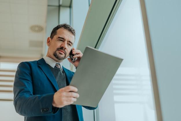 Autohändler am telefon sprechend mit kunden und autodokumenten betrachtend.