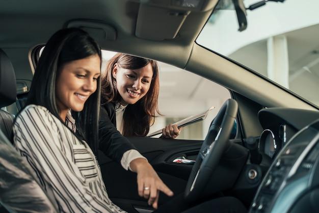 Autohändler, der dem kunden fahrzeug zeigt.