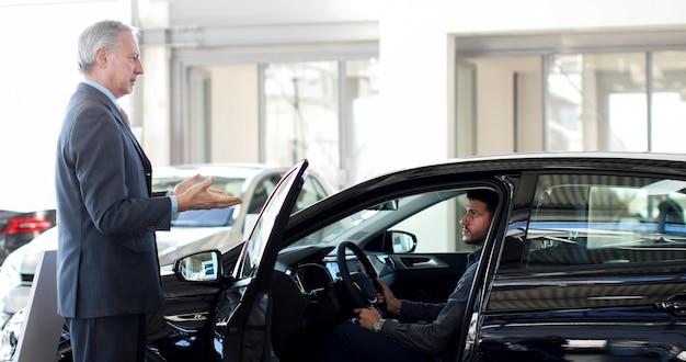 Autohändler, der einem kunden die tür eines autos öffnet