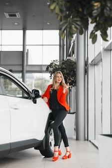 Autohändler, der einen schlüssel hält und heraus folgendes weißes auto in voller länge steht schaut.