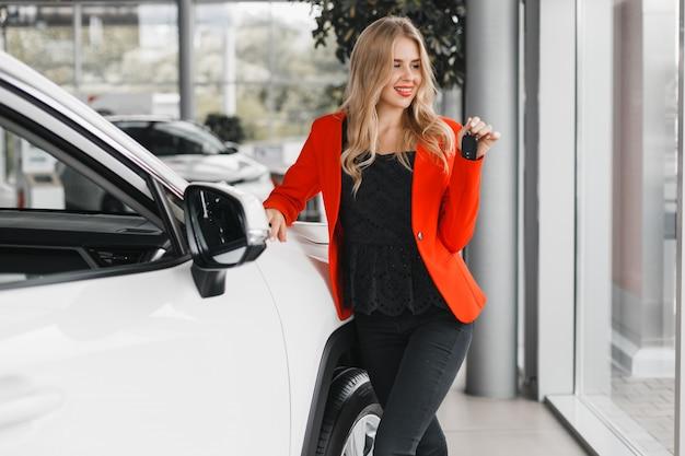 Autohändler, der einen schlüssel hält und heraus stehendes folgendes weißes auto schaut.
