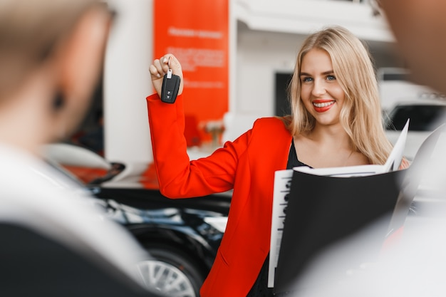 Autohändler, der einen schlüssel in ihrer hand und in breiten lächelnden nahaufnahme zeigt.