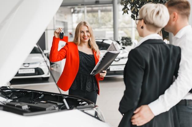 Autohändler, der einen schlüssel und dokumente und breite lächelnde stellung gegen paare hält.