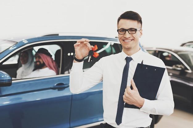 Autohändler hält schlüssel auto wird von arabern gekauft.
