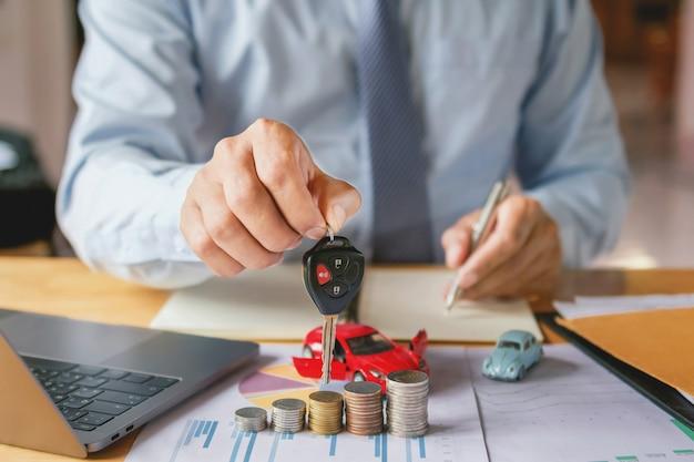 Autohändler-hand, die schlüssel hält. konzeptautoversicherung