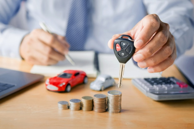Autohändler-hand, die schlüssel hält