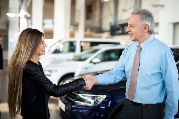 Autohändler-neuwagenkonzept, frau, die dem autohändler händedruck gibt, um den deal zu besiegeln