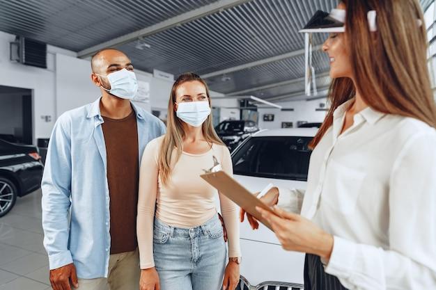 Autohändlerin, die käufer berät, die medizinischen gesichtsschutz tragen. coronavirus-jobanforderungskonzept