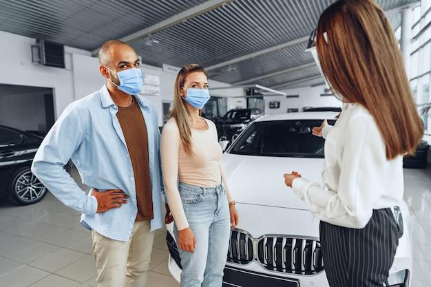 Autohändlerin, die käufer berät, die medizinischen gesichtsschutz tragen