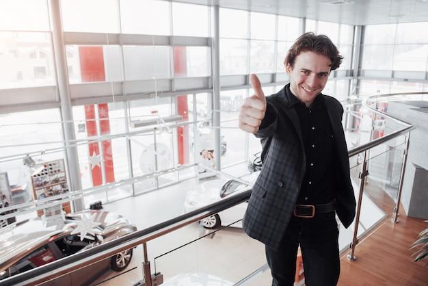 Autohaus besuchen. junger mann auf autosalon. glücklicher mann zeigt sich finger. autoverkauf und mietkonzept