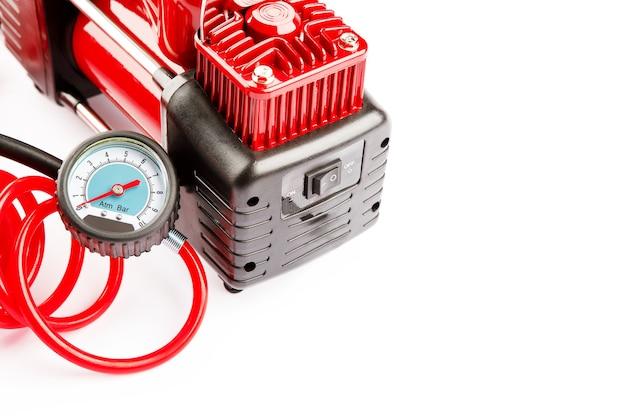 Autokompressor lokalisiert auf weißem hintergrund. die elektrische pumpe bläst ein autorad auf