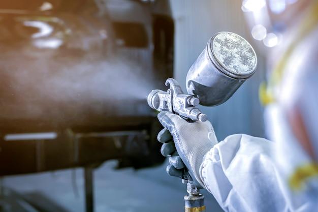 Autolackierer in schützender arbeitskleidung und atemschutzmaske, die karosserie in lackierkammer malt