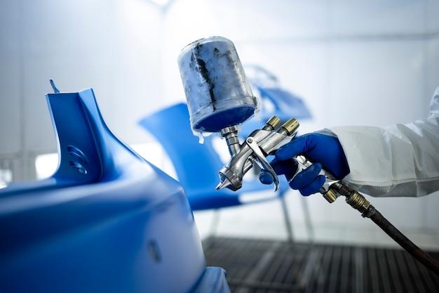 Autolackierer in schutzkleidung und maskenlackierung autostoßstange mit metallic-lack und lack in kammerwerkstatt.