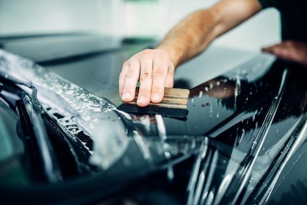 Autolackschutz, transparente filmnahaufnahme. auto vor chips und kratzern schützen. der arbeiter umhüllt die haube mit einer schutzbeschichtung
