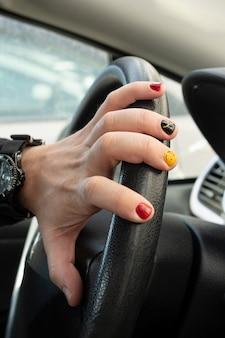 Autolenkrad und hand mit heller maniküre. ein auto fahren.