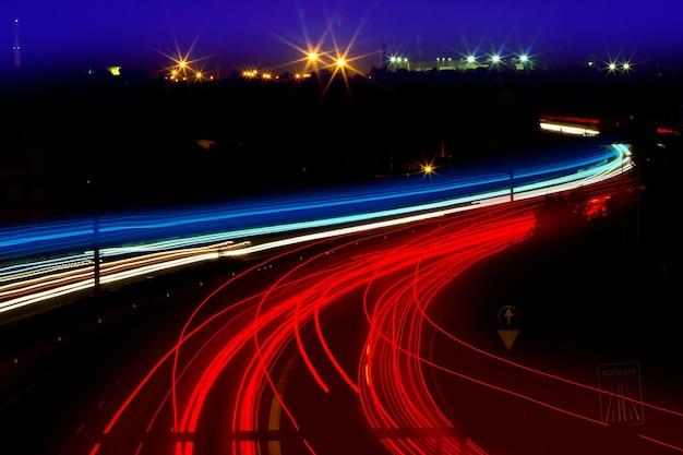 Autolichtspuren in rot und weiß auf nachtstraße