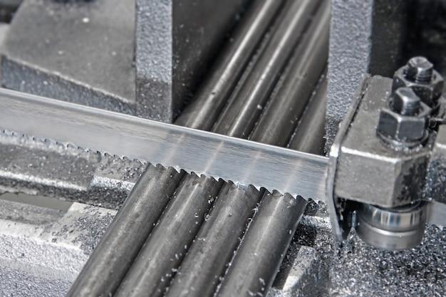 Automatische bandsäge mit kühlflüssigkeit schneidet die metallstangen des werkstücks