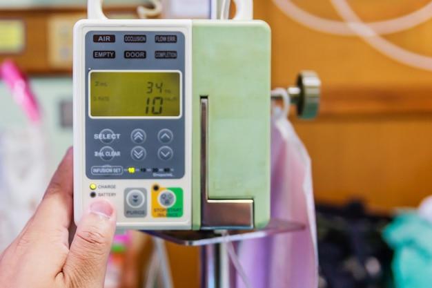 Automatische infusionspumpe und iv hängen am pfosten im patientenzimmer