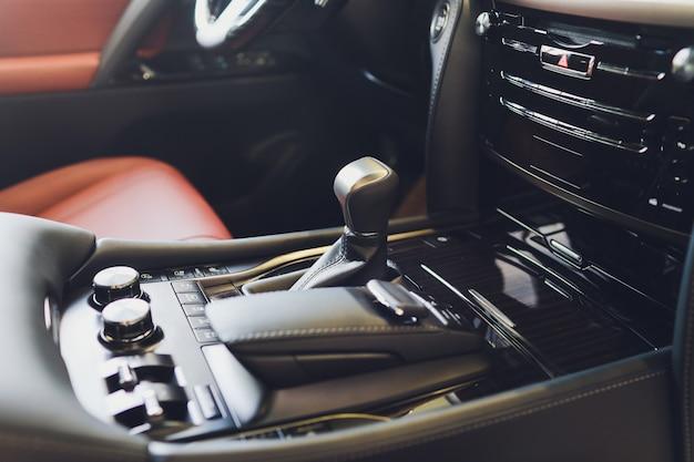 Automatische schalthebelübertragung eines modernen autos, multimedia- und navigationssteuertasten. details zum fahrzeuginnenraum. getriebeschaltung.