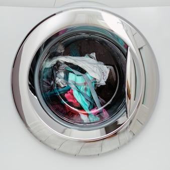 Automatische waschmaschine mit runder durchsichtiger türklappe, durch die sie farbiges leinen sehen können.