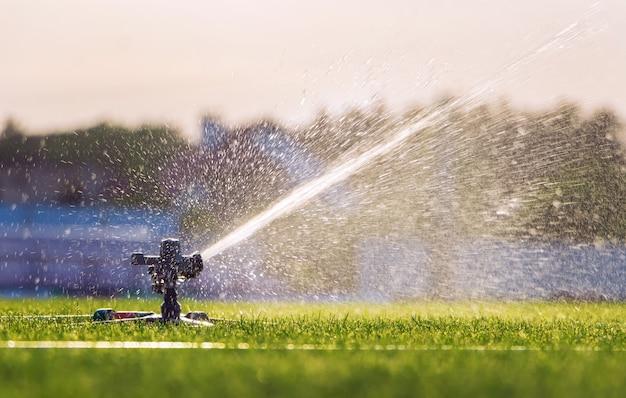 Automatischer rasensprinkler, der grünes gras auf einem stadion wässert. bewässerungssystem.