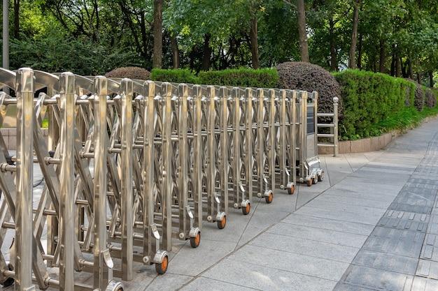 Automatisches barrier gate aus edelstahl oder faltzaun zum schutz im außenverkehr, der die straße blockiert.