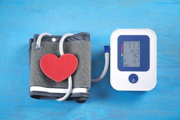 Automatisches blutdruckmessgerät und rotes herz auf blauem hintergrund.