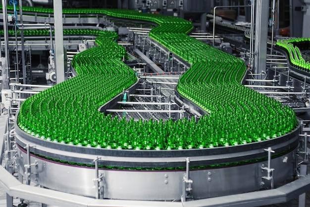 Automatisierte förderstrecke in einer brauerei. reihen von grünen glasflaschen auf einem förderband.
