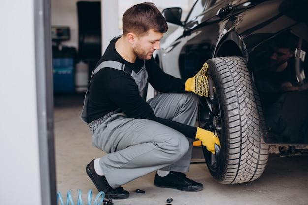 Automechaniker beim radwechsel im auto