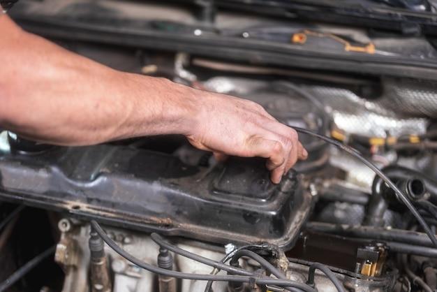 Automechaniker, der an automotor am reparaturdienst arbeitet. nahaufnahme.