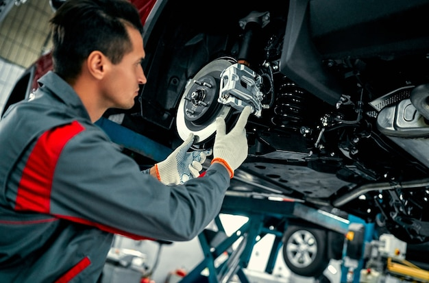 Automechaniker, der aufhängung des angehobenen automobils an autowerkstatt-werkstatt repariert