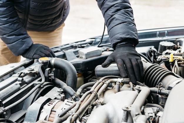 Automechaniker, der das auto repariert und die wartung umfassend überprüft. der automechaniker in handschuhen hat eine störung im autoreparaturservice festgestellt.